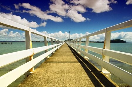 Close up view of pier and blue sky in the background. Bridge for pedestrians in the middle of the sea.