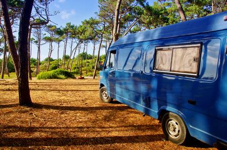 Ansicht eines blauen Packwagens mitten in Natur. Camping im Wald. Campervan-Reisekonzept. Standard-Bild - 91249672