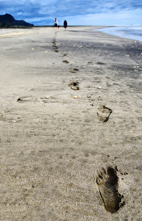 Close up of footprints in the sand on the beach. Two people walking on the beach.  Stock fotó