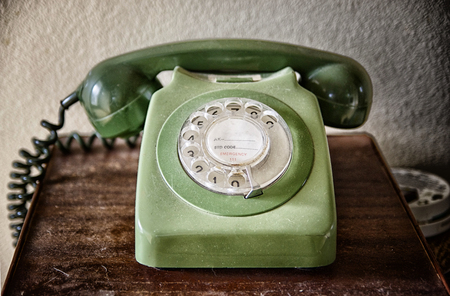 Close up of an old telephone on the table. Vintage telephone with rotary dial. Communication concept. Archivio Fotografico