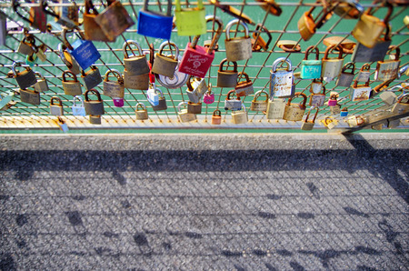 Close up of a lot of love lock on the railing. Blurred pathway in the background. Love lasts forever.  Sajtókép