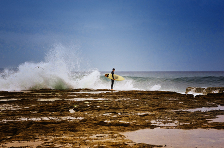 Surfing concept. Man standing on the rocks and holding a surfboard.
