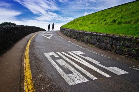 Abschluss oben des großen Zeichens auf der Straße. Geben Sie Konzept vor. Blauer Himmel und zwei Leute, die in den Hintergrund gehen. Transportsicherheit. Standard-Bild - 91689673