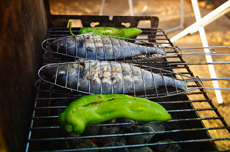Close up of grill with fishes and peppers on it. Summer barbecue party. Stock fotó