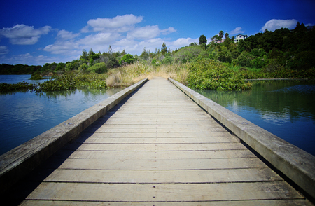 Travelling concept. Wooden pier close up, Lake, nature and blue sky in the background. Stock fotó