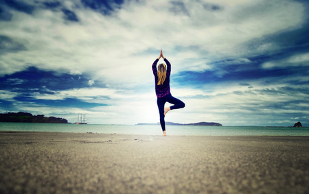 Yoga woman on the beach. Blue cloudy sky in the background.