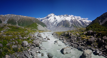Beautiful natural landscape. Rocks, river and snowy mountains in the background. Walking the Hooker Valley Track, Mount Cook, New Zealand. Enjoy the summer. Hiking and walking in the nature. Breathtaking landscape.