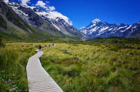 Beautiful landscape of walkway in the nature, mountains in the background. Walking the Hooker Valley Track, Mount Cook, New Zealand. Enjoy the summer. Hiking and walking in the nature. Breathtaking landscape. Stock fotó