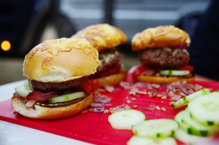 Close up of three hamburgers on the chopping board on the camping table.  Stock fotó