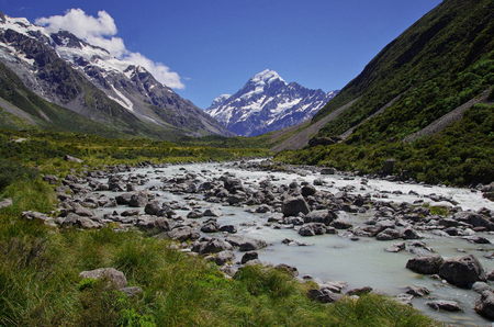 Beautiful natural landscape. Rocks, river and snowy mountains in the background.