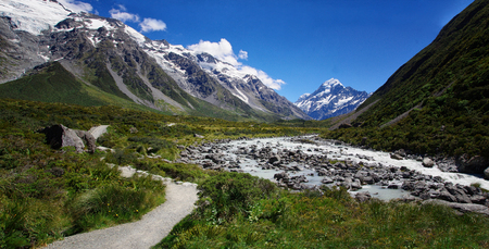 Beautiful natural landscape. Rocks, river and snowy mountains in the background. Walking the Hooker Valley Track, Mount Cook, New Zealand. Hiking and walking in the nature.