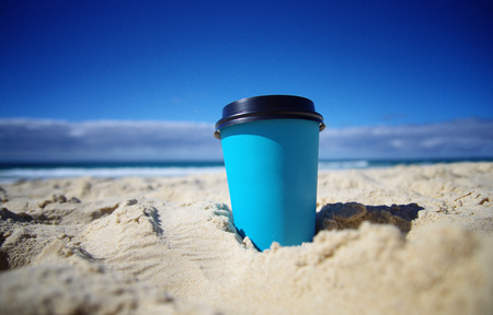Paper mug in the sand. Coffee time on the beach. Blue sky in the background. Paper coffe cup. Coffee take away.