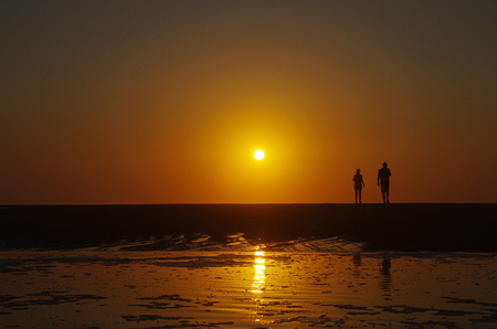 Silhouette of a couple walking on the beach, sunset in the background. Beautiful beach sunset. Holiday happiness. Standard-Bild - 115922553