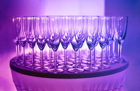 Close up of empty prosecco glasses for welcome drink. Purple and pink party light.