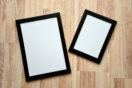 Top view of two black frames on the wooden floor. Blank frame mockups.