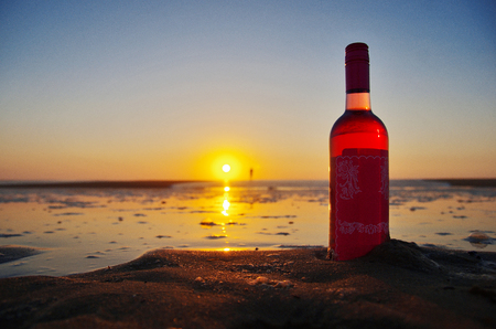 Close up of bottle of rose wine on the beach. Drinking on the beach concept.