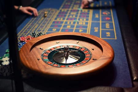 Roullette players in casino. Close up of roulette wheel and chips in the background. Imagens