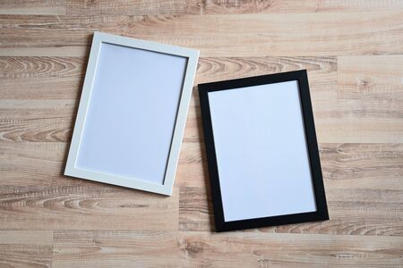 Top view of two photo frames on the wooden floor. Blank frame mockups.