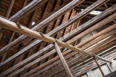 Aged beams in an old barn. Old roof achitecture detail. Wooden timbers.