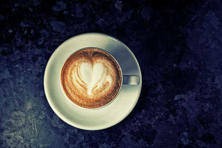 Top view of cup of cappuccino on the table. Morning coffee. Hipster cafe concept. Vintage coffee. Standard-Bild