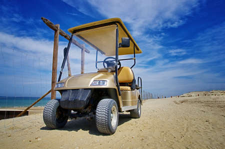 Front view of a golf cart parked along the sandy beach. Transportation vehicle. Golf cart. Summer on the beach. Standard-Bild