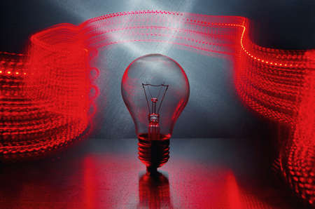 Power and light. Light bulb and red light in motion. Long exposure. Standard-Bild