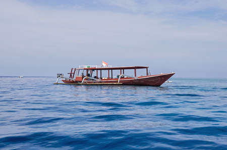 View of wooden fishing boat. Beautiful clear water in the ocean, blue sky in the background.