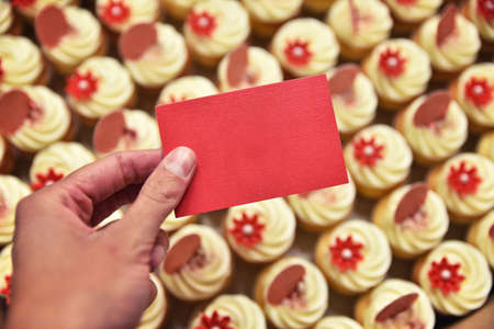 Cupcakes in the box and hand with blank card. Confectionery company. Empty business card. Standard-Bild