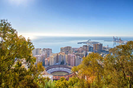 Bull arena in the middle of Malaga cityscape, port and blue sky in the background. Malaga, Andalusia, Spain.