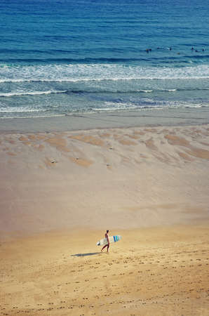 View on the beach from the rock above. Surfer walks with a surfboard. Ocean and surfers in the background. Sandy beach. Surfing concept.