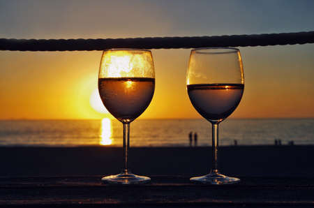 Close up two glasses of white wine, sunset on the beach in the background. Drink on the beach. Romantic evening.