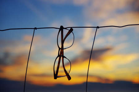 Close up of glasses hanging on the fence. Cloudy sky and beautiful sunset.