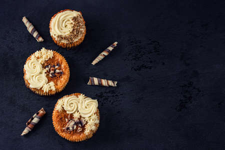 Top view of small cheesecakes. Mini chessecakes with creamy topping and chocolate shavings. Composition with blank space for a text.