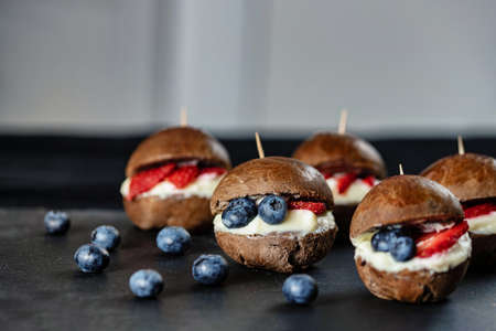 Original recipe. Choco burger with strawberries and blueberries. Small sweet burgers. Stock fotó