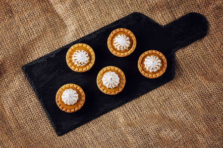 Top view of mini tartalets on a slate chopping board. Five tartalets with orange curd and meringue on the top. Sweet desserts. Sweet catering.