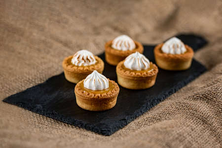 Close up view of mini tartalets on a slate chopping board. Five tartalets with orange curd and meringue on the top. Sweet desserts. Sweet catering.