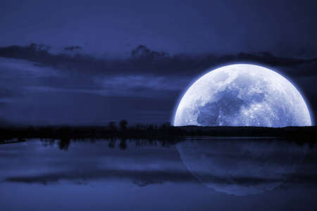 Moon over the lake, blue water and sky  Stock Photo