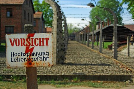 Warning board and electric fence in German death camp Auschwitz-Birkenau, Poland