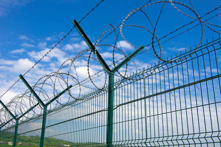 Barbed fence  against a blue sky