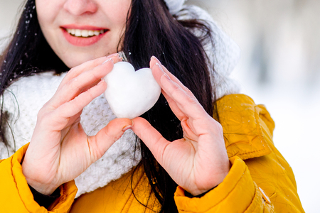freezed: Heart of snow in the hands of a girl. Winter on the street.