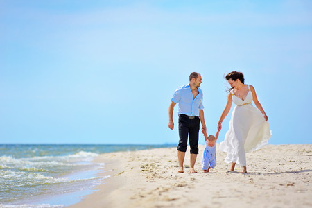 Mother and father with their toddler son walking together on a quiet beach