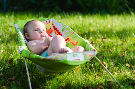 0 6 months: Peaceful baby in the rocking chair on the nature, on grass