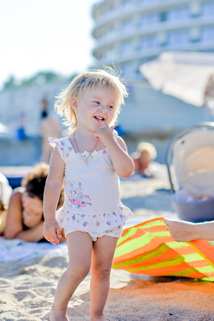 imagines: a little girl stands on the beach in the sand, imagines Stock Photo