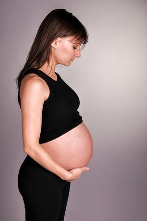 envisage: Pregnant girl in studio on dark background Stock Photo