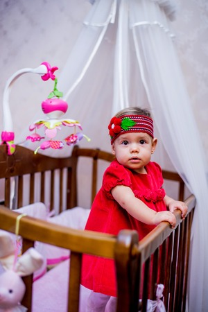 blessedness: little girl stands in her crib. Stock Photo