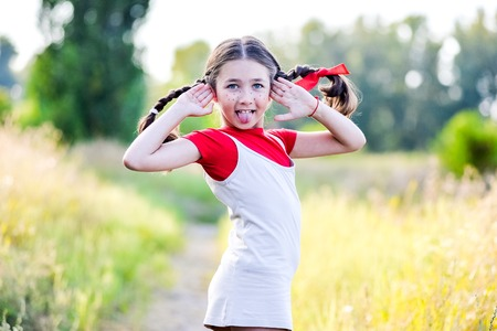 outrage: A funny cute outdoor portrait of a little girl presenting Pippi Longstocking and showing out out her tongue.