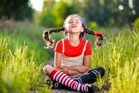 A funny cute outdoor portrait of a little girl making facial gestures. Stock Photo