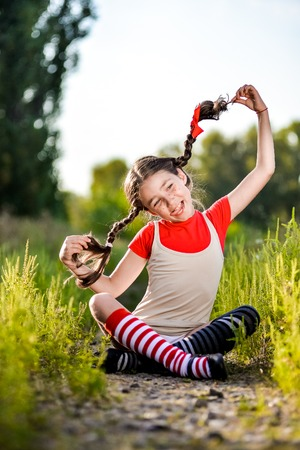 reckless: A funny cute outdoor portrait of a little girl presenting Pippi Longstocking and showing out out her tongue.