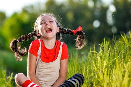 naughty girl: naughty girl with pigtails, opens his mouth and shouts, the summer on the nature