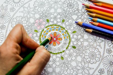autocuidado: Antiestr�s libro para colorear en el proceso de dibujo. Mujer pinta el razukrashki sobre la mesa son l�pices de colores, y el t�, el caf�